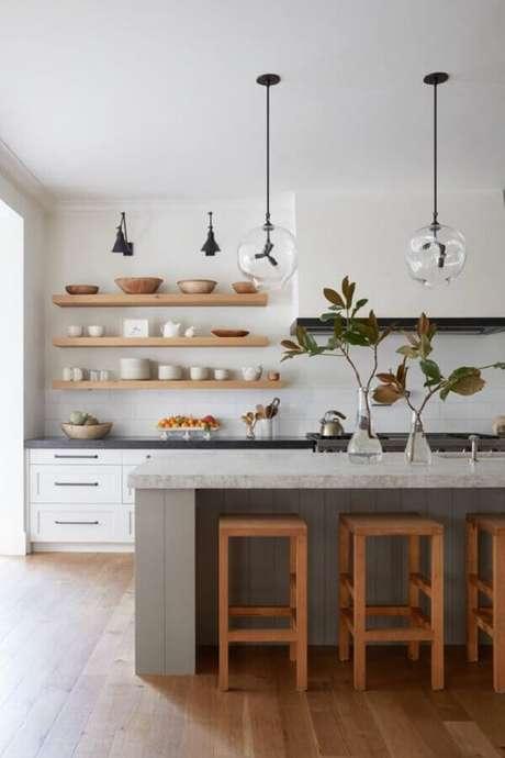 44. Cozinha com ilha decorada com banquetas de madeira para bancada. Foto: McGee & Co.