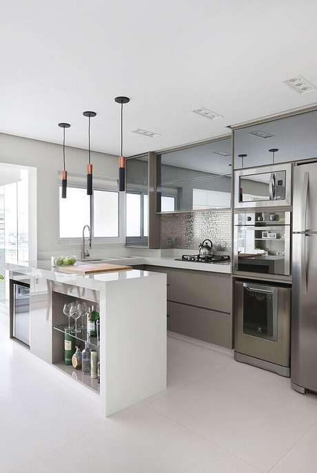 54. Decoração de cozinha planejada com armários espelhados e luminária pendente moderna para bancada – Foto Pinterest
