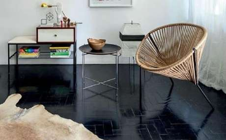 25. Sala decorada com poltrona rústica e piso pintado de preto – Foto Jeito de Casa