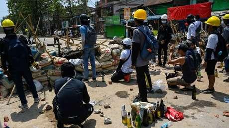 Manifestantes atrás de barricadas no município de Thaketa, em Yangon, na sexta-feira
