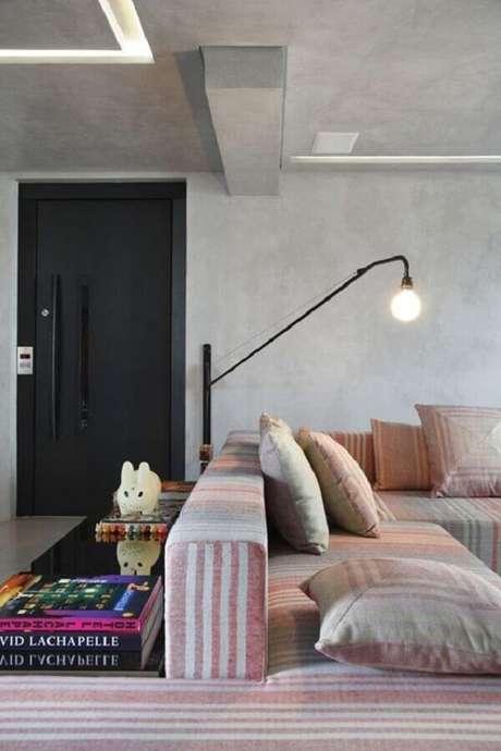 40. Sala de estar decorada com cimento queimado e luminária de parede moderna – Foto Fashionismo