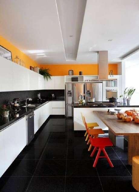 15. Piso preto para cozinha ampla decorada com cadeiras coloridas para ilha – Foto Houzz