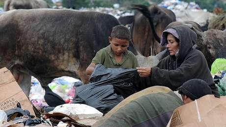 690 milhões de pessoas passaram fome em 2019, de acordo com a FAO. Na foto, uma mulher e uma criança procuram comida no meio do lixo