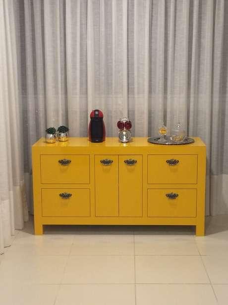 36. O aparador amarelo para sala serve de apoio para cafeteira. Fonte: Giselle Jaeger Silva de Moraes