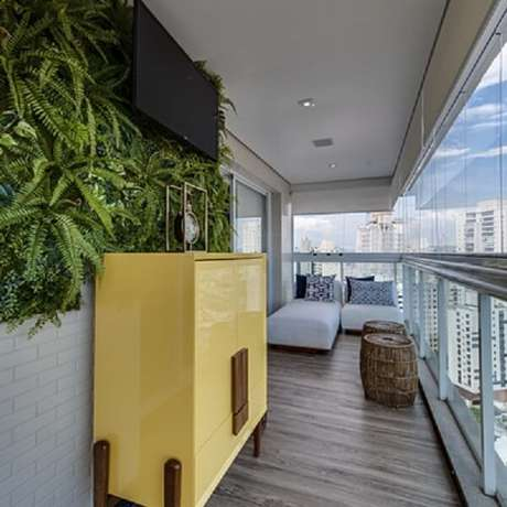 34. O aparador amarelo foi posicionado na varanda do apartamento. Fonte: Habitissimo