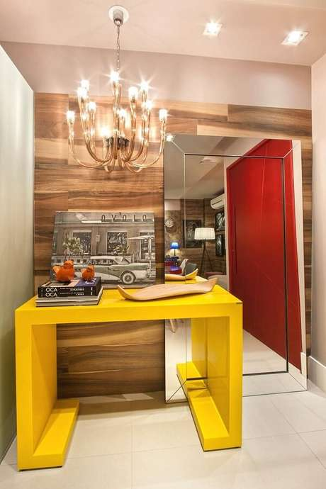 29. O aparador amarelo com espelho de chão decoram o hall de entrada do imóvel. Fonte: Gerson Dutra de Sá e Ana Lucia Salama