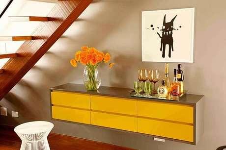 28. Modelo de aparador bar amarelo suspenso otimiza o espaço do cômodo. Fonte: Roberto Robl