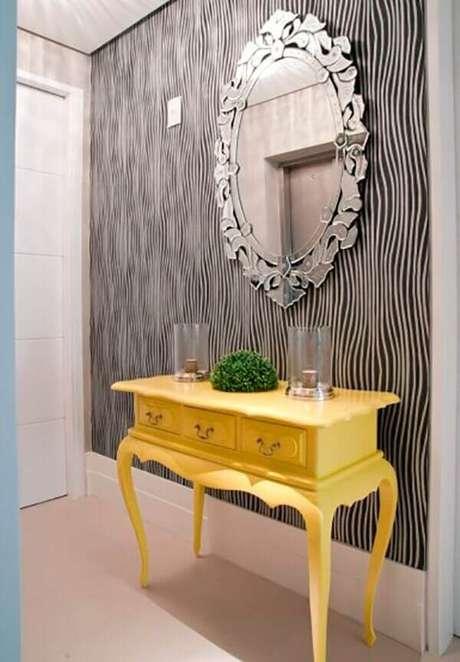 30. O aparador amarelo com espelho fixado na parede decora a entrada da casa. Fonte: Pinterest