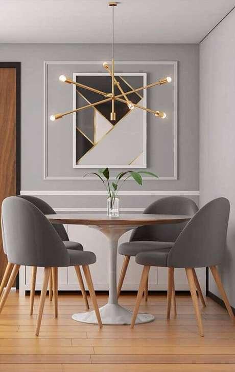 6. Decoração com luminária moderna e cadeiras estofadas para mesa de jantar em sala pequena – Foto: Home Fashion Trend