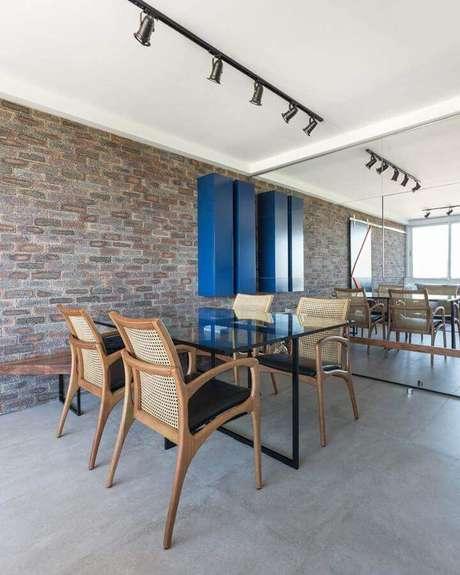 67. Decoração de sala com parede tijolinho e cadeiras de madeira para mesa de jantar de vidro – Foto: Casa de Valentina