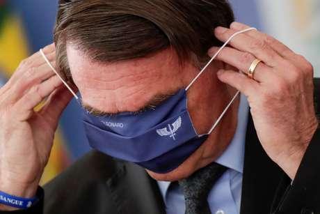 Presidente Jair Bolsonaro tenta colocar máscara durante evento no Palácio do Planalto 22/03/2021 REUTERS/Ueslei Marcelino
