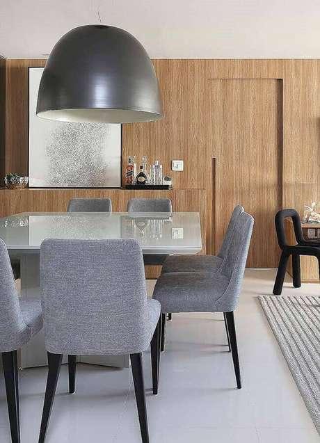 19. Decoração de sala de jantar com parede amadeirada e cadeiras estofadas para mesa de jantar – Foto: Histórias de Casa