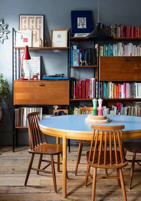 46. Decoração de sala com estante para livros e cadeiras para mesa de jantar de madeira – Foto: Andreas Móveis