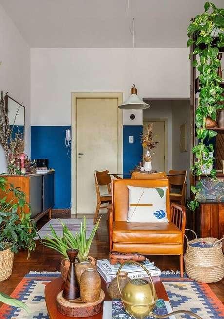54. Sala simples decorada com vasos de plantas e poltrona marrom de couro – Foto: Histórias de Casa