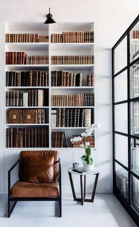 41. Poltrona marrom escuro moderna para decoração de cantinho de leitura com estante planejada para livros – Foto: Futurist Architecture