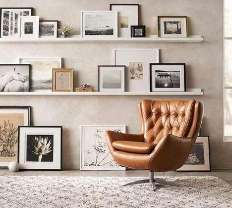 43. Poltrona marrom giratória para sala decorada com prateleiras para quadros – Foto: Pinterest