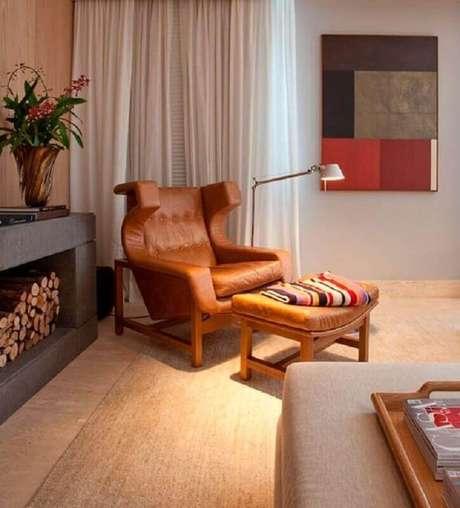 50. Sala de estar decorada com lareira e poltrona marrom moderna – Foto: Histórias de Casa