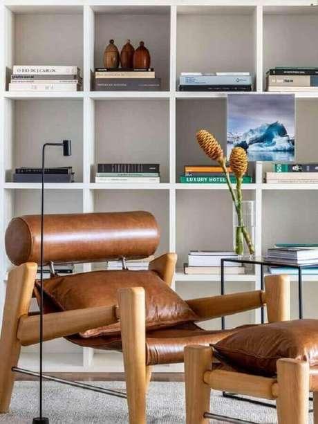 55. Poltrona marrom moderna para decoração de sala com estante branca de nichos – Foto: Casa de Valentina
