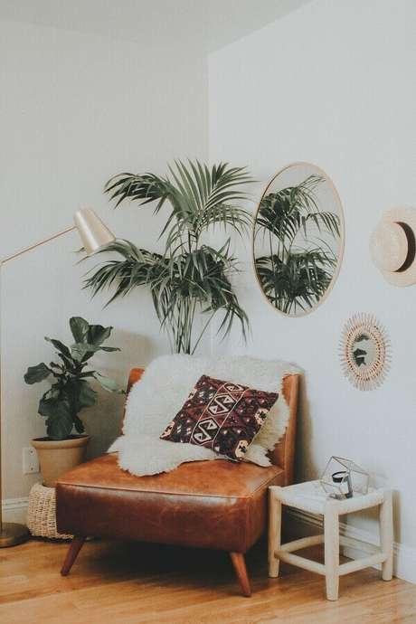 30. Sala decorada com poltrona de couro marrom e vasos de plantas – Foto: Pinterest