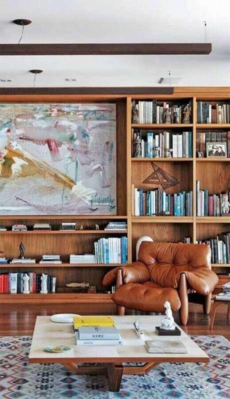 33. Sala decorada com estante de madeira para livros e poltrona de couro marrom – Foto: Pinterest