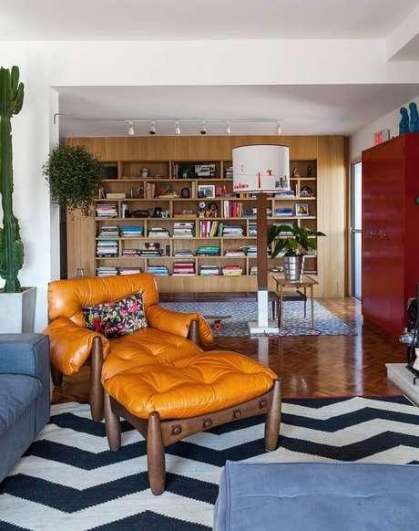 52. Sala decorada com tapete chevron preto e branco e poltrona marrom de madeira – Foto: Histórias de Casa