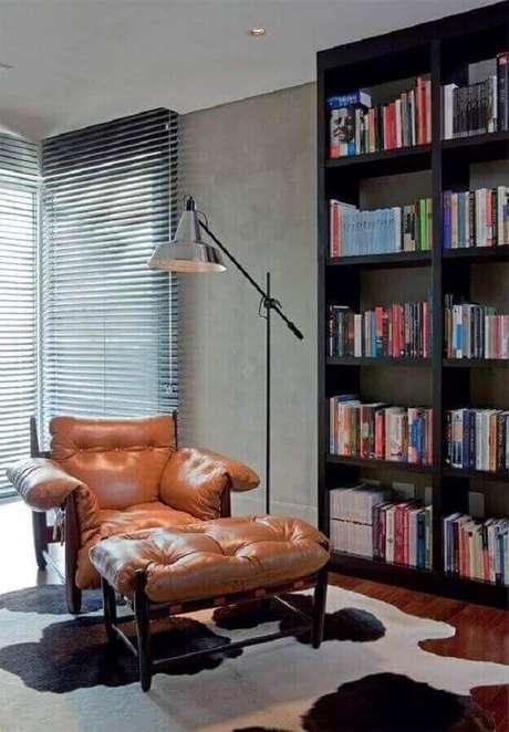 34. Decoração de cantinho de leitura com confortável poltrona marrom e estante de livros preta – Foto: Pinterest
