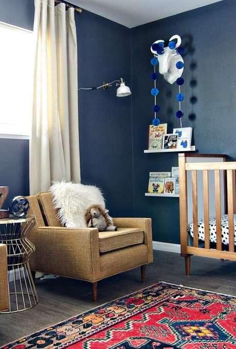 63. Quarto de bebê azul marinho decorado com berço de madeira e poltrona de amamentação – Foto: Pinterest