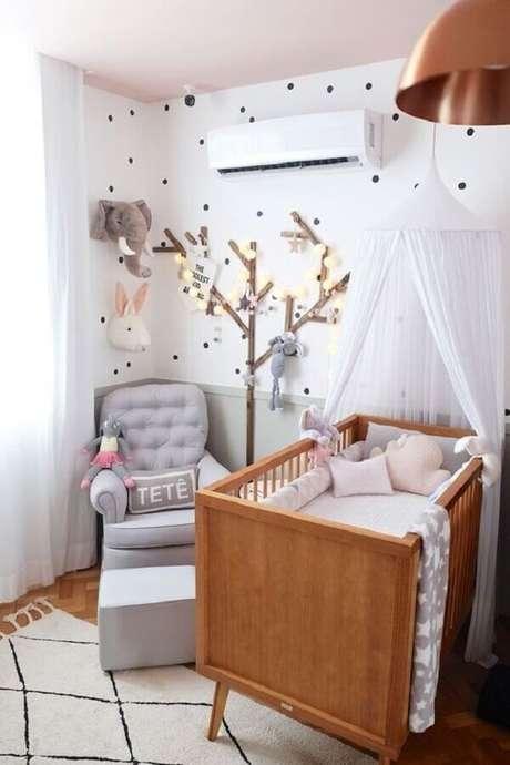 68. Quarto de bebê decorado com berço de madeira e poltrona de amamentação com puff cinza – Foto: Casa de Valentina