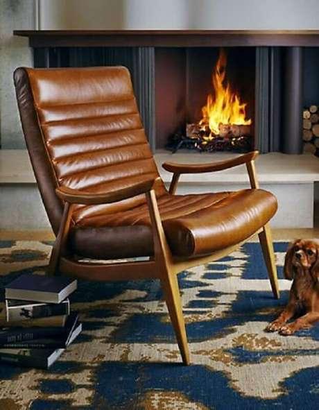 35. Sala com lareira decorada com poltrona marrom de couro – Foto: Pinterest