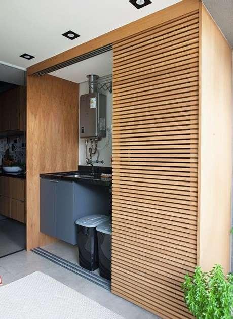24. Lavanderia escondida por uma porta de correr de madeira – Foto pinterest