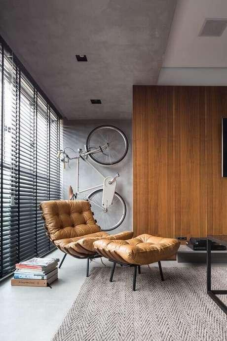 13. Decoração estilo industrial com parede de cimento queimado e poltrona marrom confortável – Foto: Futurist Architecture