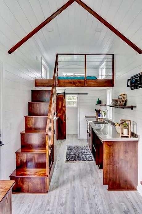 49. A escada estreita de madeira leva até a cama mezanino casal. Fonte: Deguile Móveis