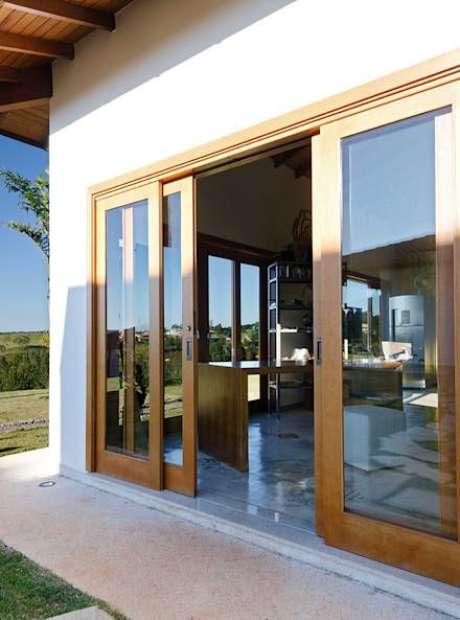 31. Porta de correr para sala com vidro e madeira para dividir a varanda – Foto Homify