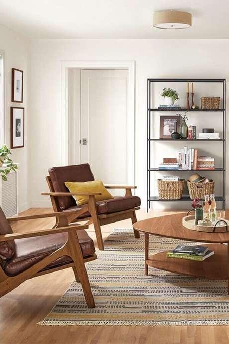 25. Poltrona marrom de madeira para sala decorada com estante estilo industrial – Foto: Room & Board