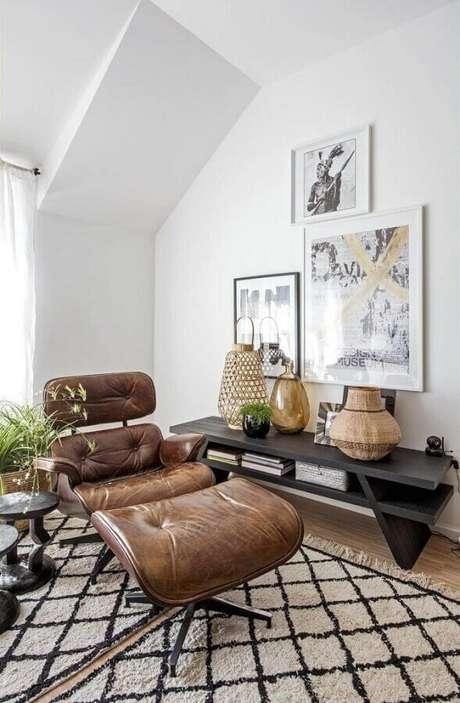20. Decoração clean para sala com aparador de madeira e poltrona marrom escuro com puff – Foto: Pinterest