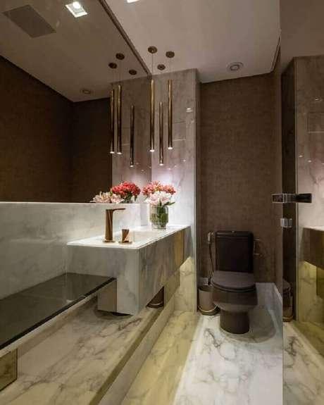10. Banheiro social de luxo decorado com bancada de mármore e luminária pendente moderna – Foto: Decor Salteado