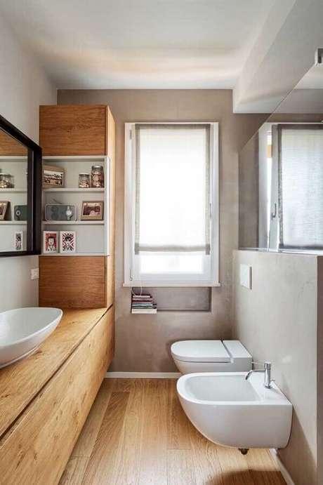 15. Banheiro social decorado com cimento queimado e bancada de madeira – Foto: Andreas Móveis