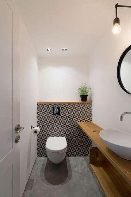 33. Modelo de banheiro social pequeno e simples decorado com bancada de madeira – Foto: Arquitrecos