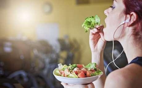 Mulher comendo salada na academia