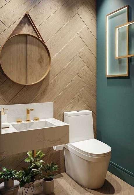 54. Parede amadeirada para decoração de banheiro social com espelho redondo – Foto: Architecture Art Designs