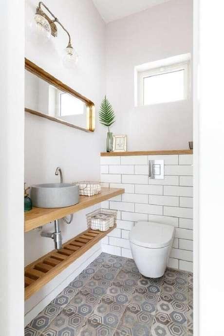 5. Bancada de madeira para banheiro social simples decorado com piso antigo – Foto: Pinterest
