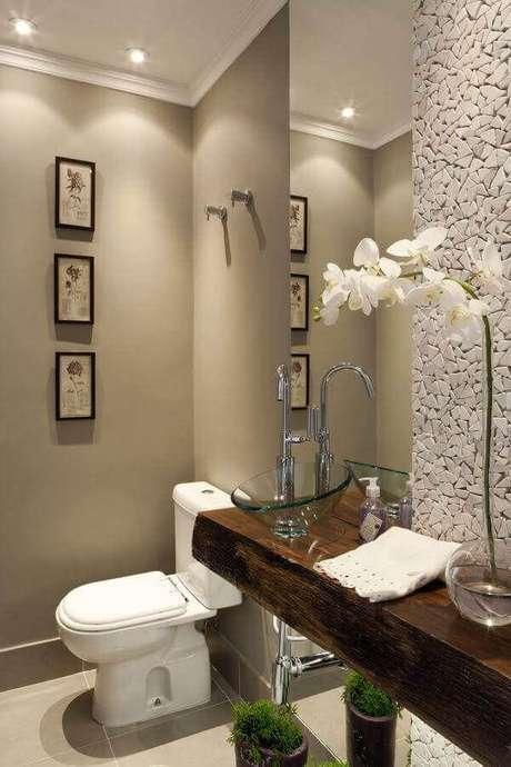 14. Bancada de madeira com cuba de vidro para decoração de banheiro social com revestimento de pedra para parede – Foto: Pinterest