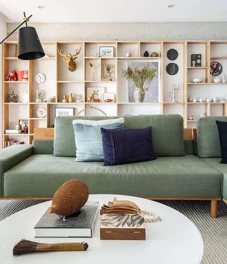 27. Sofá verde oliva para sala moderna decorada com estante de nichos de madeira – Foto: Fernando Jaeger