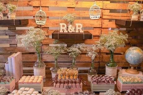 46. Decoração de noivado simples e rústico com muito docinhos e garrafas de vidro decoradas com flores mosquitinho – Foto: Pinterest
