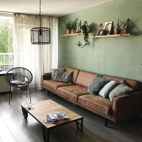 59. Parede verde oliva para sala simples decorada com sofá marrom – Foto: Pinterest