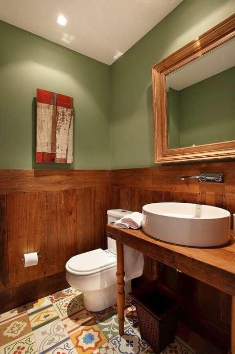13. Banheiro rústico simples decorado com bancada de madeira e parede verde oliva – Foto: Revest Acabamentos