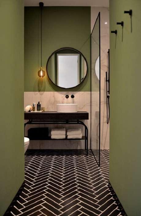 12. Decoração moderna para banheiro com parede verde oliva e espelho redondo – Foto: Arkpad