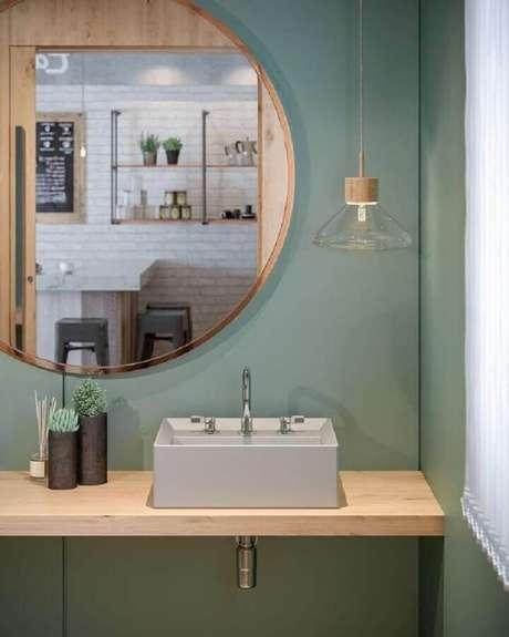 36. Parede verde oliva para banheiro decorado com espelho redondo e bancada de madeira – Foto: Archilovers