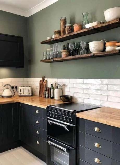 16. Cozinha preta planejada com bancada de madeira e parede verde oliva – Foto: Pinterest