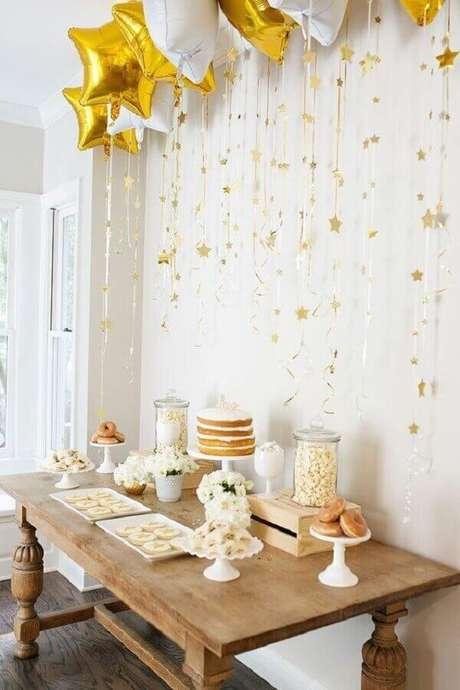 55. Aqui a festa de noivado simples ganhou vários balões em formato de estrela para formar um delicado painel sobre a mesa do bolo – Foto: Pinterest